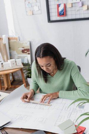 Foto de Arquitecto afroamericano concentrado midiendo plano con regla en el lugar de trabajo - Imagen libre de derechos