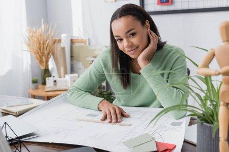 Photo pour Souriant architecte afro-américain regardant la caméra près du plan directeur sur le bureau, au premier plan flou - image libre de droit