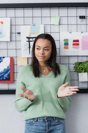 Photo pour Jeune designer d'intérieur afro-américain geste tout en se tenant près de peintures sur le mur - image libre de droit