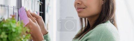 Photo pour Vue recadrée du designer d'intérieur afro-américain fixant une note collante sur le mur, premier plan flou, bannière - image libre de droit