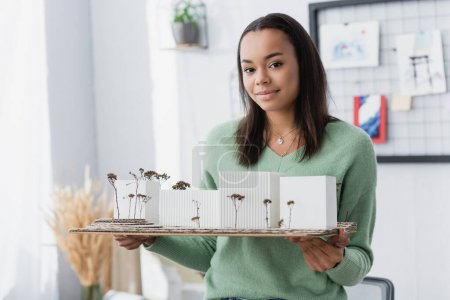 Photo pour Souriant afro-américaine tenant maquette architecturale tout en regardant la caméra - image libre de droit