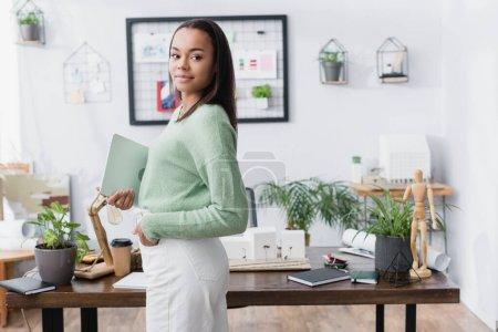 Photo pour Architecte afro-américain souriant debout avec la main dans la poche et tenant un ordinateur portable - image libre de droit