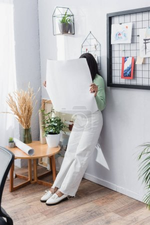 african american architect obscuring face with paper while leaning on wall at home
