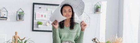 Photo pour Jeune architecte afro-américain couvrant la tête avec le plan tout en regardant loin à la maison, bannière - image libre de droit