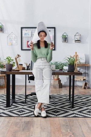 Photo pour Souriant designer d'intérieur afro-américain couvrant la tête avec un plan près du bureau à la maison - image libre de droit