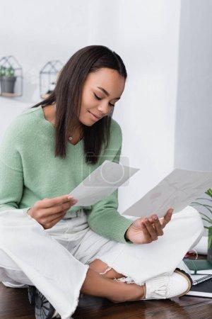Photo pour Un designer d'intérieur afro-américain souriant regardant des tableaux assis sur un bureau avec des jambes croisées - image libre de droit