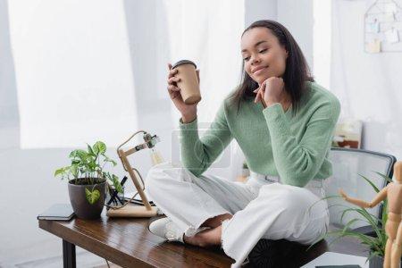 Photo pour Positive, rêveuse architecte afro-américain tenant café à emporter assis sur le bureau avec les jambes croisées - image libre de droit