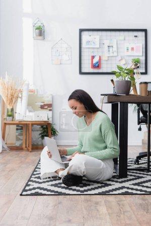 Afrikanisch-amerikanischer Innenarchitekt tippt auf Laptop, während er zu Hause auf dem Boden sitzt
