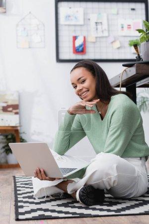 Photo pour Joyeux designer d'intérieur afro-américain souriant à la caméra tout en étant assis sur le sol avec ordinateur portable - image libre de droit