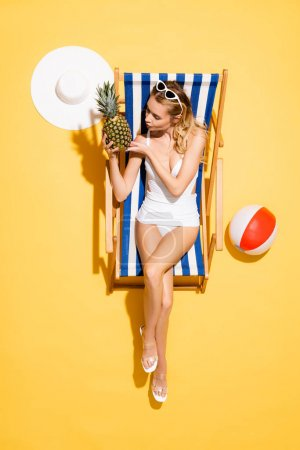 Photo for Top view of young woman with fresh pineapple sitting in deck chair near inflatable ball and straw hat on yellow - Royalty Free Image