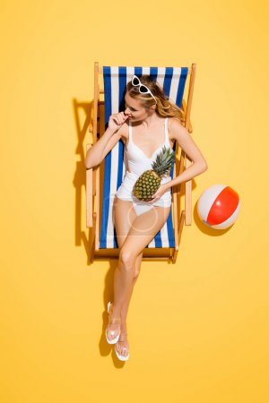 top view of woman in swimsuit with hand near face holding pineapple while resting in deck chair near inflatable ball on yellow