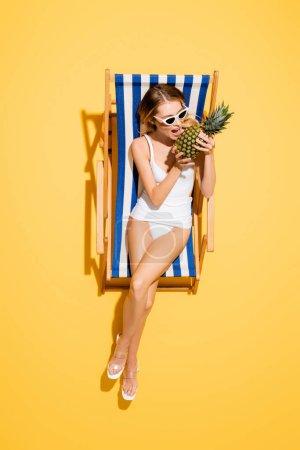 vue de dessus de la femme en maillot de bain et lunettes de soleil mordant l'ananas entier tout en se reposant dans la chaise longue sur jaune