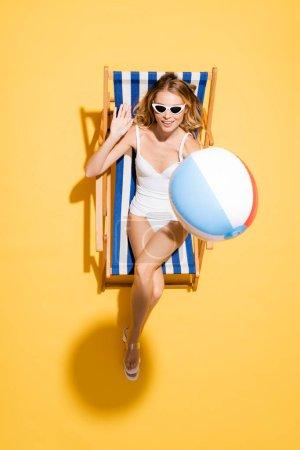 vista superior de mujer joven en gafas de sol y traje de baño agitando la mano mientras se relaja en la silla de cubierta con bola inflable en amarillo