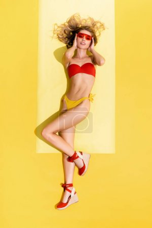 top view of slim woman touching face and looking at camera while sunbathing on yellow