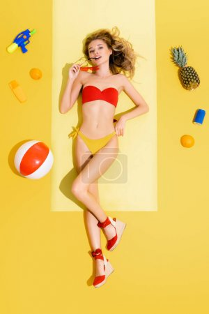 Photo for Top view of young woman holding eyeglasses while relaxing on beach mat near fruits, can of soda, inflatable ball and water gun on yellow - Royalty Free Image