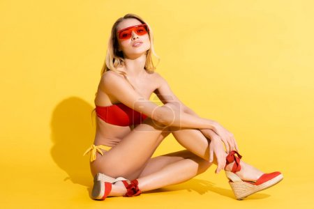 Photo for Young woman in swimwear and sandals looking at camera while sitting on yellow - Royalty Free Image