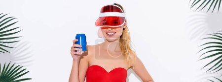 Photo pour Femme gaie dans la visière du soleil souriant à la caméra tout en tenant une canette de soda sur blanc, bannière - image libre de droit