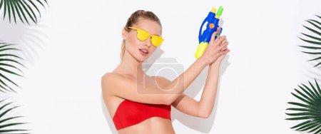 mujer joven en gafas de sol amarillas posando con pistola de agua cerca de hojas de palma en blanco, pancarta