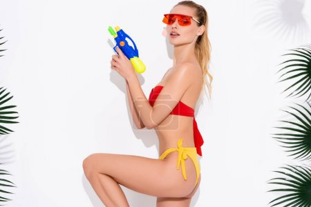 Photo for Young woman in sunglasses and swimwear looking at camera while standing with water gun on white - Royalty Free Image
