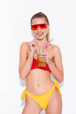 Photo for Joyful woman in swimsuit and sunglasses drinking refreshing cocktail while looking at camera on white - Royalty Free Image