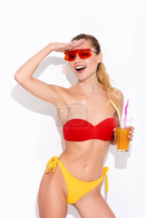 Photo for Excited woman in swimsuit looking away while holding refreshing cocktail on white - Royalty Free Image