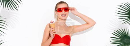 Photo for Happy woman touching eyeglasses and smiling at camera while holding ice cream on white, banner - Royalty Free Image