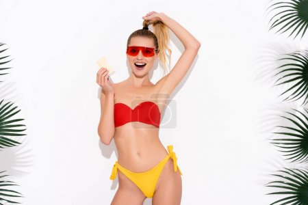 Photo for Excited woman in swimwear and sunglasses touching hair while holding ice cream on white - Royalty Free Image