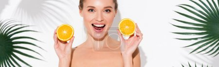 astonished woman looking at camera while holding halves of fresh orange on white, banner