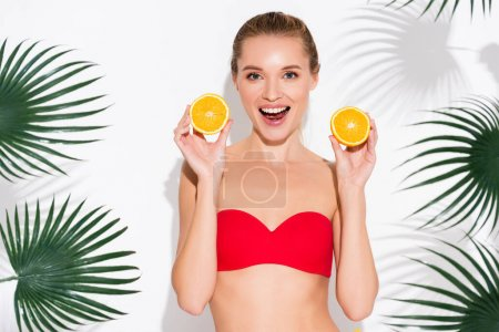 Photo for Excited woman in swimsuit holding halves of ripe juicy orange near palm leaves on white - Royalty Free Image