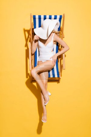 Photo for Top view of slim woman in swimsuit obscuring face with straw hat while sitting in deck chair on yellow - Royalty Free Image