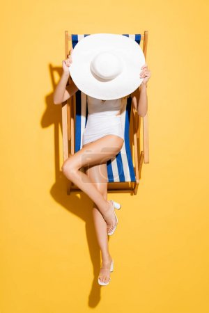 top view of woman in swimsuit obscuring face with straw hat while sitting in deck chair on yellow