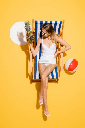 Photo for Top view of woman with hand on hip holding fresh pineapple while relaxing in deck chair near straw hat and inflatable ball on yellow - Royalty Free Image