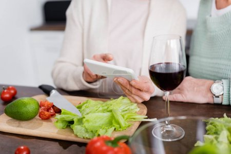 cropped view of senior women using smartphone near vegetables on table