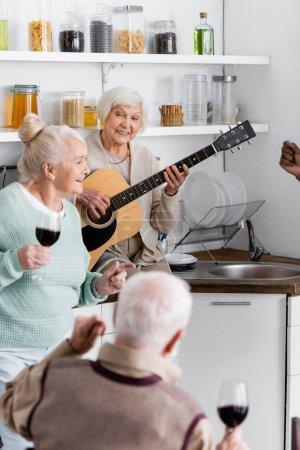 Photo pour Heureuse retraitée jouant de la guitare acoustique près des amis interracial seniors dans la cuisine - image libre de droit