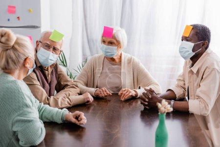 Photo pour Retraités dans des masques médicaux avec des notes collantes sur les fronts jouer à un jeu avec des amis interracial - image libre de droit