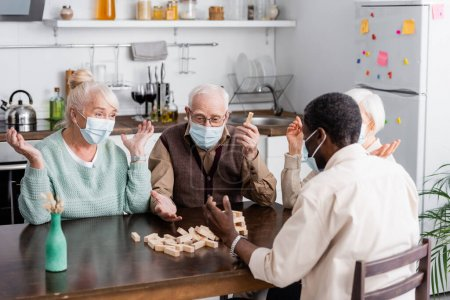 retired multiethnic people in medical masks playing tower wood blocks game at home