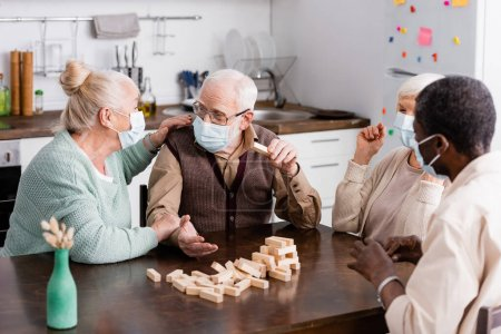 retired multicultural people in medical masks playing tower wood blocks game at home