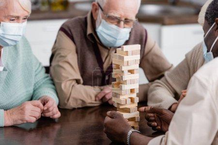 pensionierter afrikanisch-amerikanischer Mann in medizinischer Maske spielt in der Nähe von Freunden ein Holzklötzchen-Spiel auf verschwommenem Hintergrund