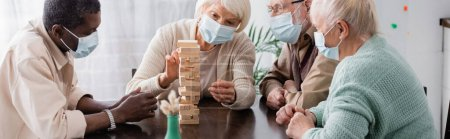 retired multicultural people in medical masks playing tower wood blocks game at home, banner
