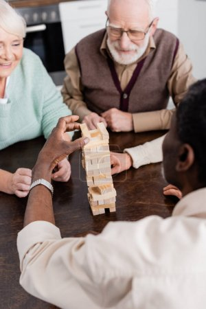 retired african american man playing tower wood blocks game near happy senior friends on blurred background