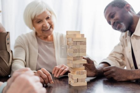tower wood blocks on table near happy multicultural pensioners on blurred background