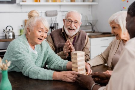 amazed retired woman playing tower wood blocks game near cheerful multicultural friends