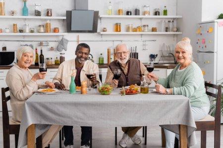 Photo pour Heureux interracial retraités tenant des verres avec du vin rouge près de savoureux déjeuner sur la table - image libre de droit