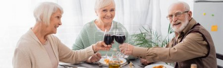 happy senior friends clinking glasses with red wine near tasty lunch on table, banner