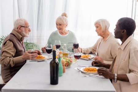 Photo pour Heureux amis multiculturels et aînés parler tout en ayant délicieux déjeuner près de verres de vin rouge - image libre de droit
