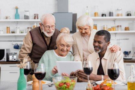 Photo pour Personnes âgées multiculturelles regardant tablette numérique avec des amis heureux près de la nourriture savoureuse sur la table - image libre de droit