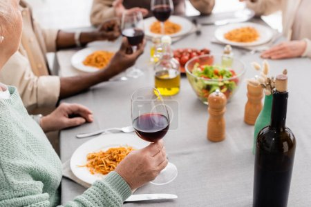 cropped view of senior woman holding glass of red wine near plate with pasta during lunch with multicultural friends