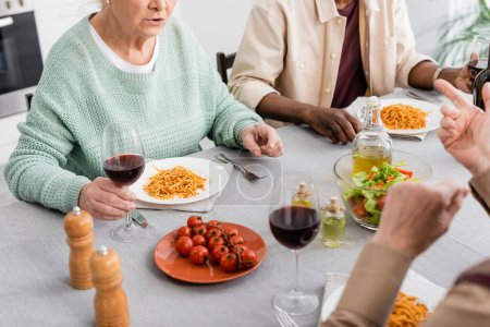 cropped view of senior woman holding glass of red wine while talking during lunch with multicultural friends on blurred background