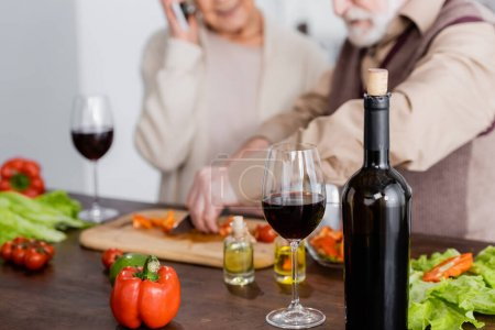 bottle with red wine near glass, vegetables and retired couple on blurred background