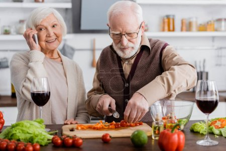 Photo for Senior man cutting vegetables near happy retired wife talking on smartphone - Royalty Free Image